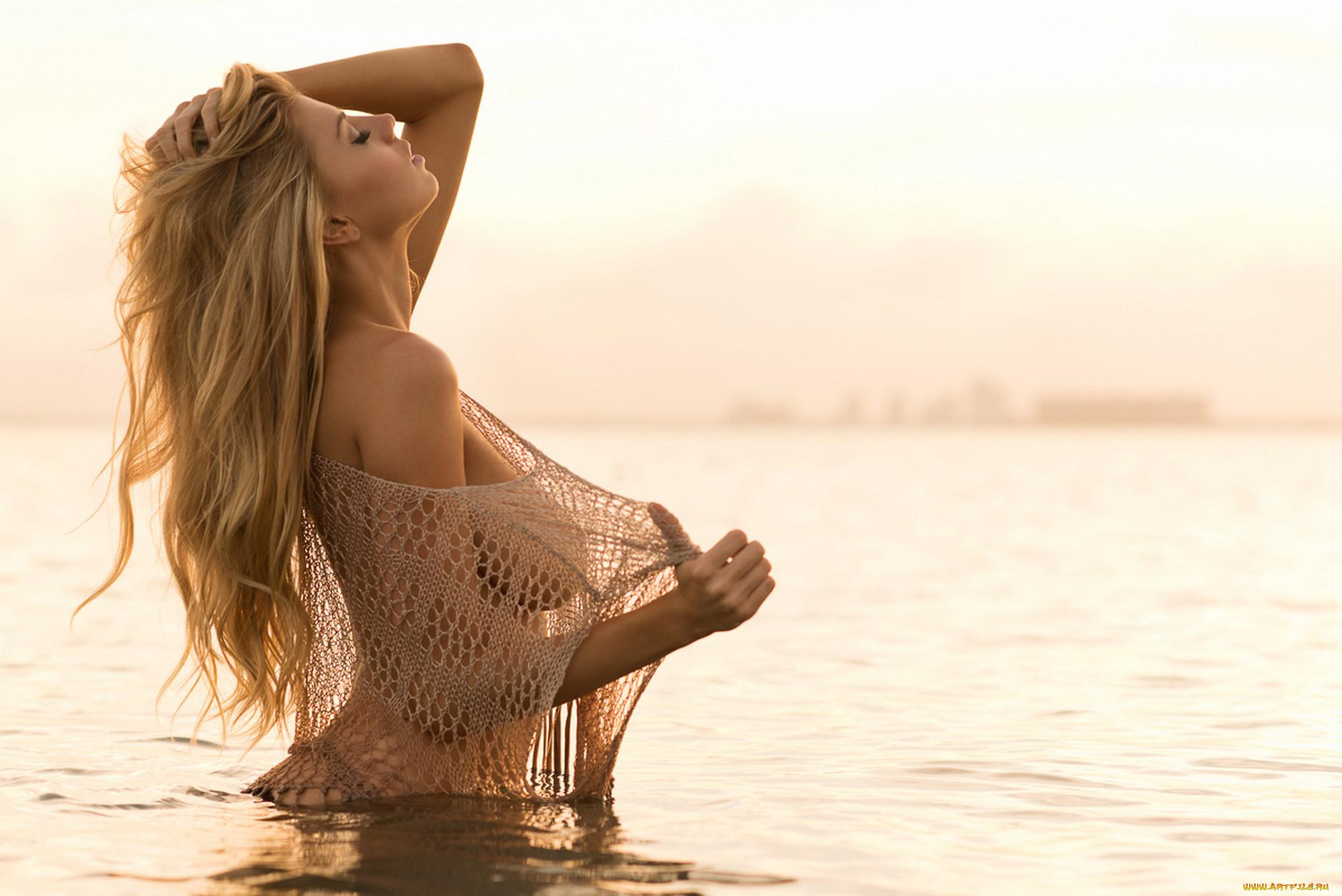 Кобыла с прекрасными титьками томно принимает солнечные ванны на нудистском пляже